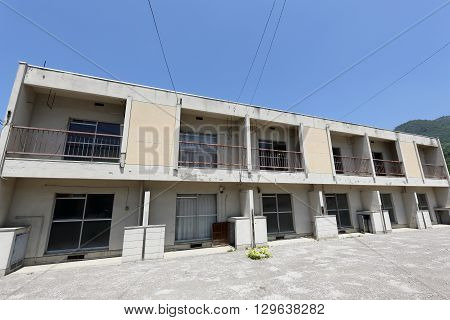 Vacant old Japanese apartment building against the blue sky