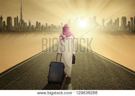 Image of Arabic businessman walking on the road while carrying luggage and wearing islamic clothes