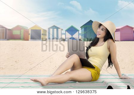 Attractive asian woman using a laptop while daydreaming on the beach