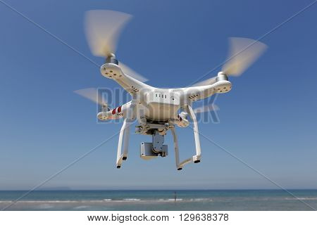 KAGAWA JAPAN - MAY 06, 2016: White remote controlled Drone Dji Phantom 3 equipped with high resolution video camera hovering in air with beach and clear blue sky in the background