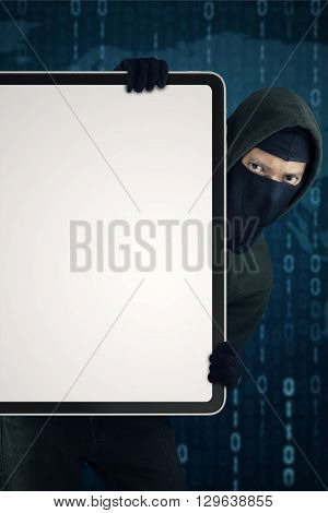 Male hacker wearing mask and holding a blank board with binary code background