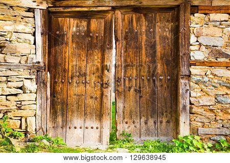 Old double rustic wooden barn doors in stone walls made from rows of nails and timber planks