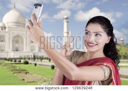 Beautiful Indian woman using mobile phone to take selfie picture at Taj Mahal