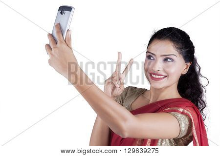 Beautiful Indian woman using smartphone to take selfie picture while wearing a saree clothes in the studio