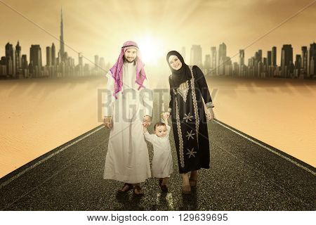 Happy middle eastern family holding hands together and walking on the road