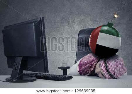 Stressful Arabic businessman sleeping on desk with Palestine flag on the bomb above his head and a computer on the table