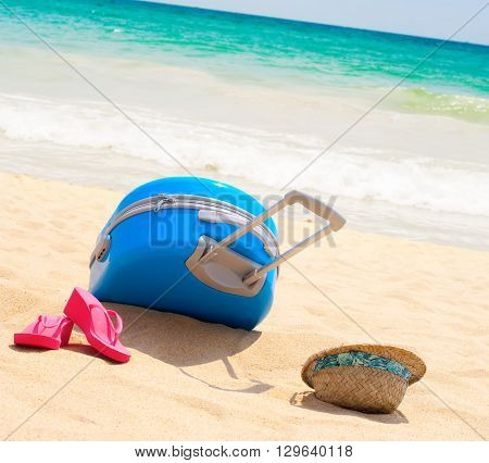 Holiday Accessories Suitcase Hat Slippers on Beach Blue Sea Yellow Sand Relax Sunny Summer Day
