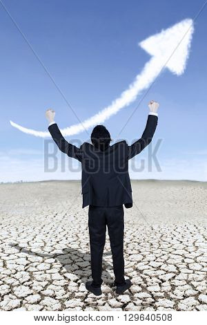 Happy businessman celebrates his success by raising his hands with upward arrow on the sky