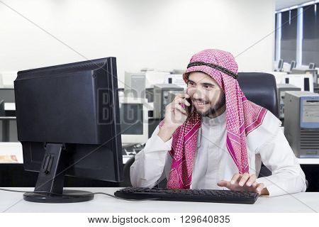 Picture of a young Arabian businessman working at the workplace with a computer and talking on the cellphone