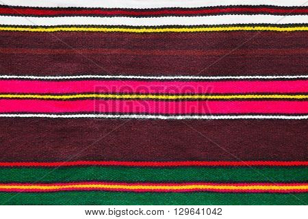 Background pattern and texture of a handmade woollen rug with colorful stripes over a dark burgundy background in a full frame view