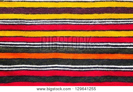 Multicolored handmade woollen rug texture with parallel stripes in red yellow black white and orange in a closeup full frame view