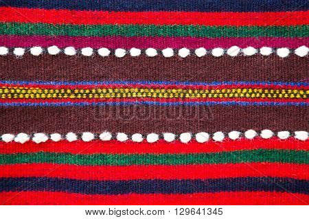 Colorful handmade Bulgarian woollen rug with a striped pattern in red green and burgundy with white dotted accents close up view in a full frame background pattern and texture