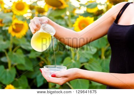 Female hand pours sunflower oil from a jug into a bowl on a background field. harvesting concept