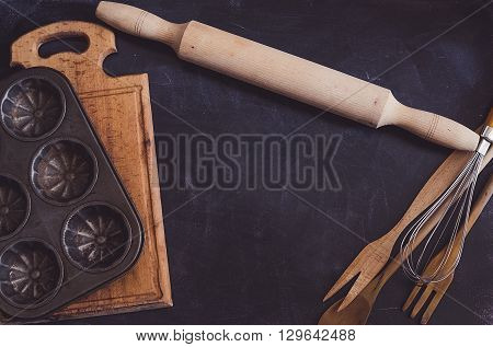 Baking concept on dark background. Baking preparation top view of variety of baking utensils. Kitchen table ware rolling pin. Background layout with free text space. Top view. Copy space.