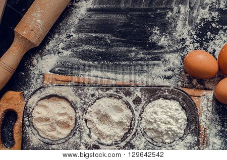 Baking concept on dark background with free text space. Baking preparation top view of variety of baking utensils with different kind of flour and eggs on chalkboard. Baking ingredients. Top view.