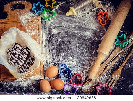 Baking children concept. Baking cookies for kids top view of variety of baking utensils with different kind of flour eggs and colorful cutters on black chalkboard. Family fun. Baby art.