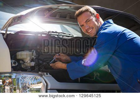 Portrait of mechanic examining the car at the repair garage