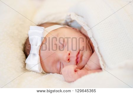 A baby girl in white headband is sleeping covered with a white blanket