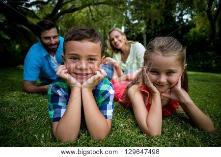 Portrait of children lying with head in hands against parents sitting in yard