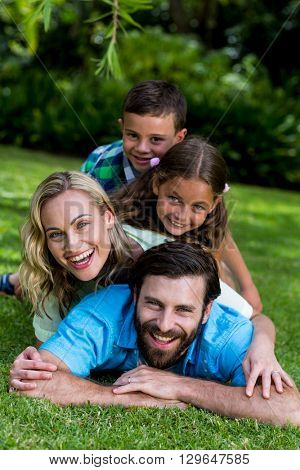 Portrait of smiling family lying on top of each other in yard