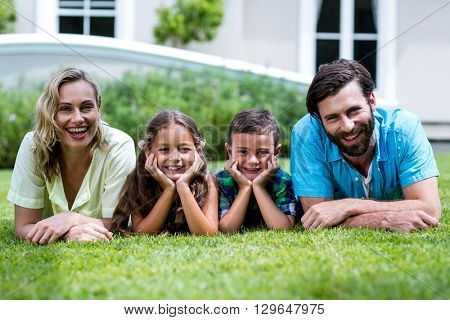 Close-up portrait of happy family lying on grass at yard