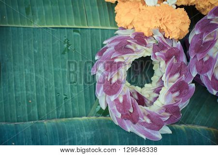 Beautiful garland jasmine and orchids and calendula flower on green banana leaf process in vintage style