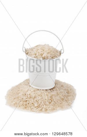 White bucket full of rice stands on a heap rice on a white background