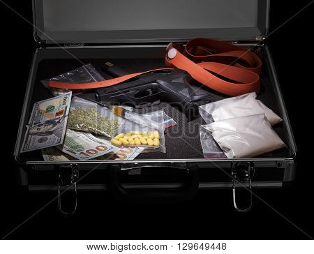 Drugs, money and a gun in a suitcase on a black background