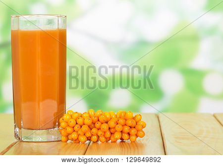 A glass of juice of sea buckthorn on a green background