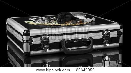 Black suitcase with gun and drug money to cover isolated on a black background