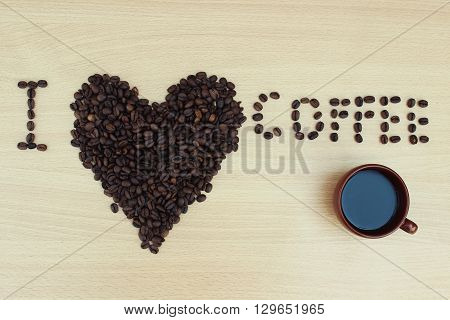 Cup of coffee and coffee beans in the form of hearts close up on a wooden background