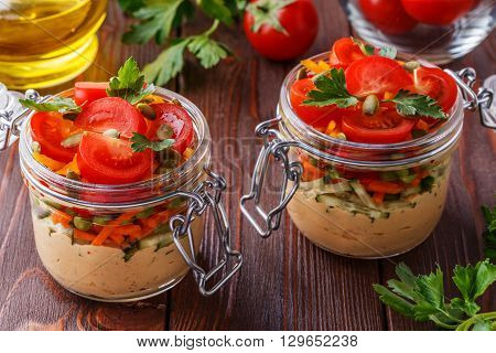 Healthy breakfast - hummus with vegetables in glass jars selective focus.