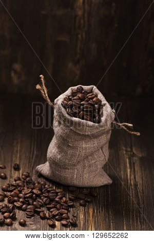 Coffee beans in burlap bags over wooden background. Vintage style. Selective focus