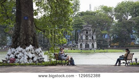 Hanoi, Vietnam - May 14, 2016: Tourist sitting on the sketch at Hoan Kiem (Sword) lake after taking a tour around old quarter streets of Hanoi capital city.