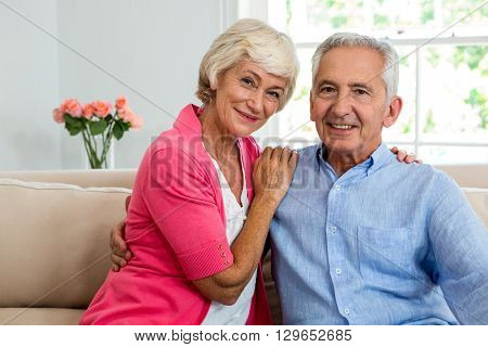 Portrait of happy senior couple with arm around while sitting on sofa