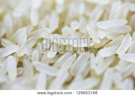 White and yellow rice grains close-up on a tablespoon in a glass