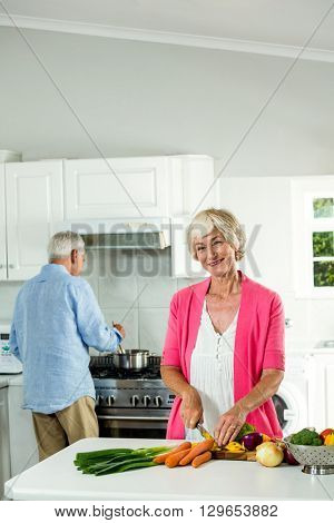 Portrait of smiling senior woman cutting vegetables in kitchen