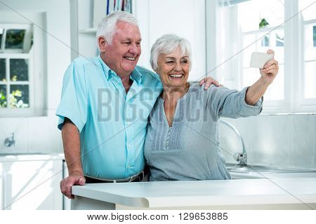 Cheerful retired couple taking selfie while standing in kitchen