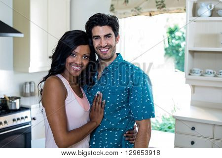 Portrait of young couple embracing each other in kitchen at home