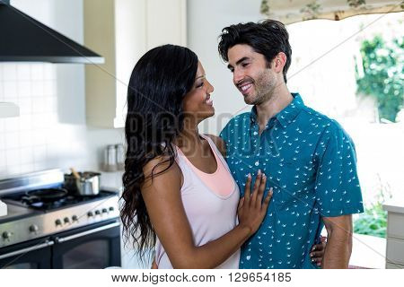 Young couple embracing face to face in kitchen at home