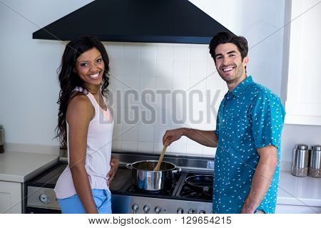 Portrait of couple cooking food together in kitchen at home