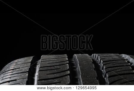 Car tires close-up Winter wheel profile structure on black background