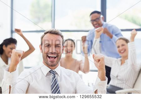 Portrait of businessman celebrating success in office with her colleagues