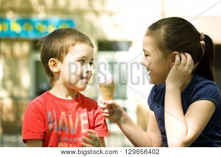 Girl is feeding his little brother with ice-cream. Outdoor