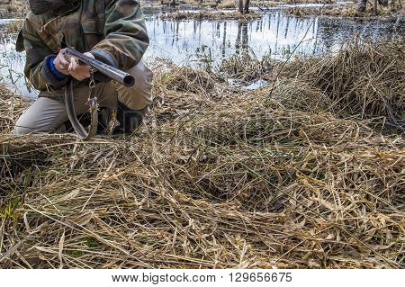 The hunter sits on the swamp in the forest and holding an old hunting rifle