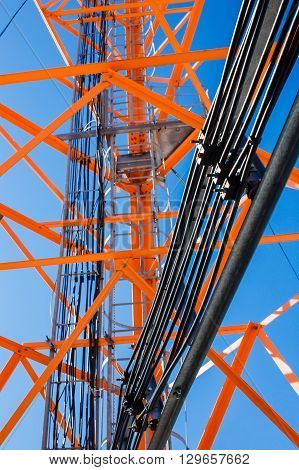 telecommunications tower with feeder cables. orange metal structure tower wire feeder track, stairs, poles. closeup. bottom view