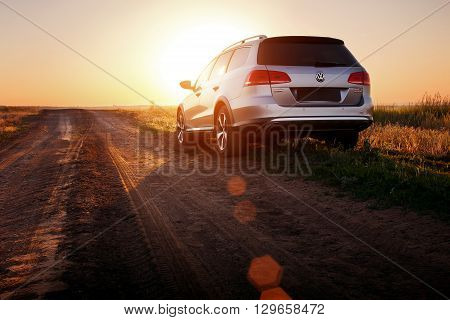 Saratov, Russia - June 02, 2014: Grey car Volkswagen Passat stay on dirt road at sunset