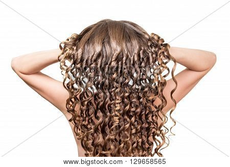 The girl raises her long curly hair, closeup on white background
