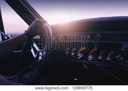 Man holding steering wheel inside car at sunset