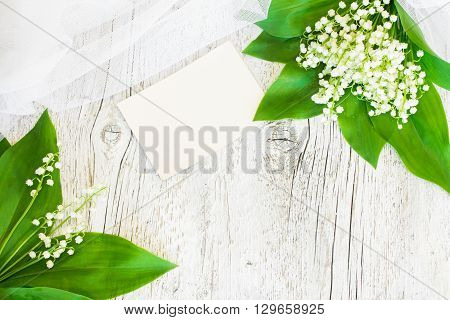 bouquet of lilies of the valley with a veil on an old white wooden background with a blank sheet of white paper